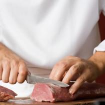Metzger Wendl beim schneiden eines Fleisches von glücklichen Tieren